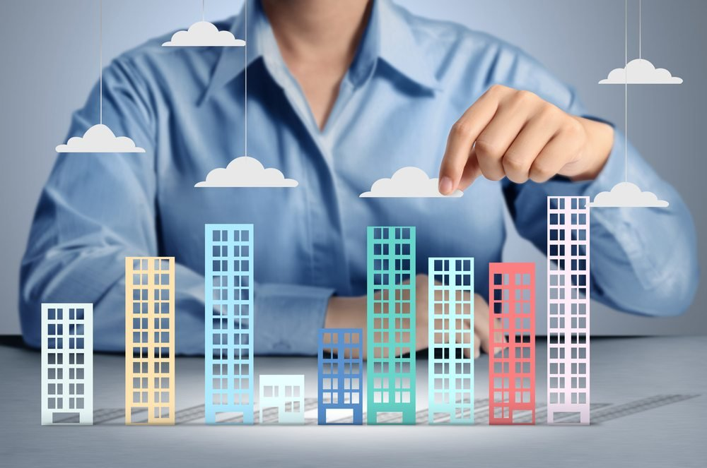 Buttonwood Property Management- a picture of a person in a professional sitting at a table with a 3D diagram of a collection of buildings in front.